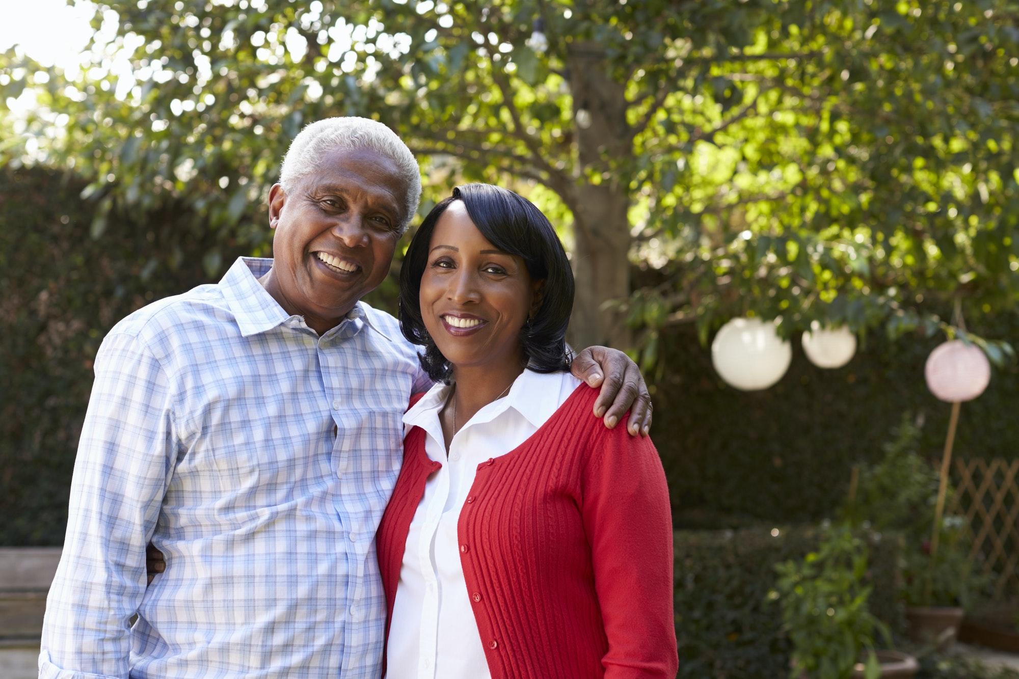 Senior black couple in their garden looking to camera